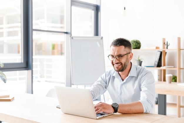 Vrolijke office man 30s in wit overhemd zit aan bureau en werkt op laptop in business center