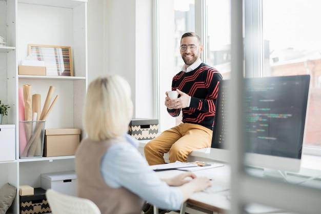 Vrolijke office man koffie drinken tijdens een gesprek met coder
