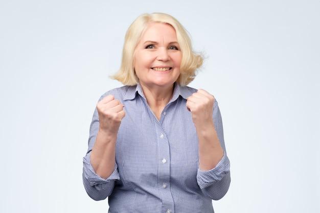 Vrolijke oma met brede glimlach die vuisten opheft