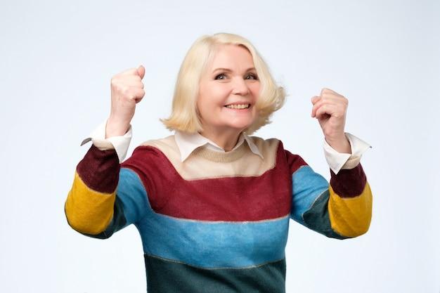 Vrolijke oma met brede glimlach stak handen op en toont succesvol teken
