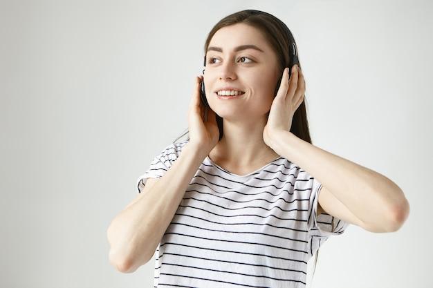 Vrolijke onbezorgde jonge donkerharige vrouw van in de twintig die binnenshuis ontspannen in vrijetijdskleding en draadloze hoofdtelefoons