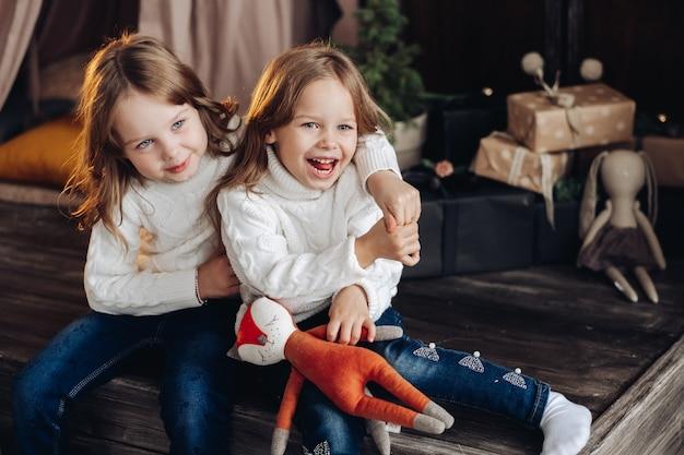 Vrolijke, onbezorgde meisjes in witte gebreide truien en spijkerbroeken die elkaar omhelzen en plezier maken. kerstmis.