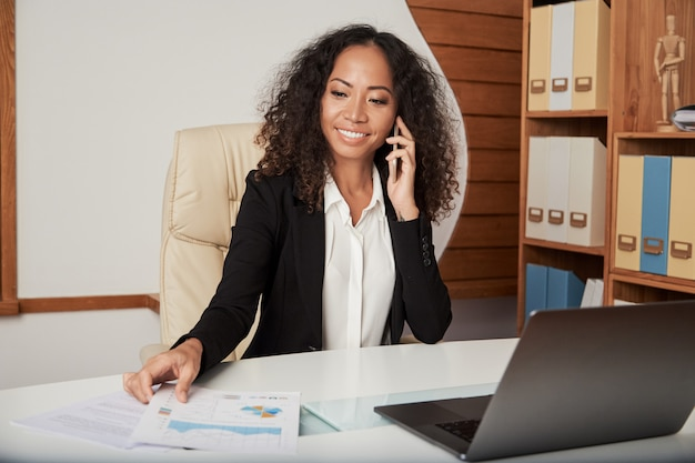 Vrolijke onderneemster die telefoongesprek in bureau hebben