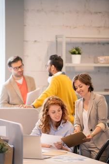 Vrolijke ondernemende jonge dames verkooprapport bekijken en bespreken nieuw project in kantoor van bedrijf