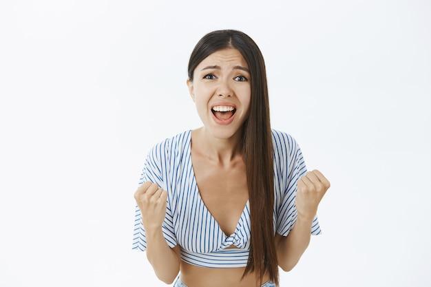 Vrolijke ondersteunende en opgewonden vrouwelijke fan in bijgesneden gestreepte blouse balde vuisten