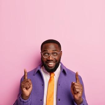 Vrolijke ongeschoren man wijst beide wijsvingers omhoog, toont een geslaagd idee, promoot kopie ruimte, draagt een bril, een oranje stropdas en een paarse jas