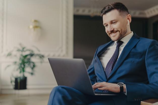 Vrolijke ongeschoren welvarende mannelijke ondernemer werkt op laptopcomputer werkt op afstand heeft videoconferentie gekleed in formeel pak met stropdas poseert bij gezellig interieur belt partner via online chat