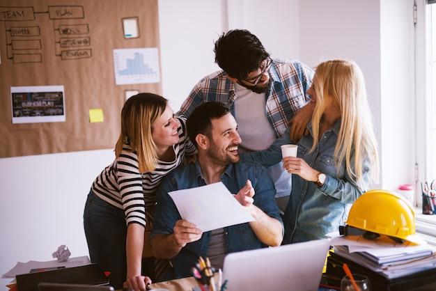 Vrolijke ontwerpers praten over nieuwe zaken in hun kantoor.