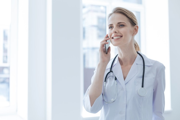 Vrolijke opgetogen jonge dokter die geniet van werkuren in het ziekenhuis terwijl hij vreugde uiting en een gesprek aan de telefoon voert