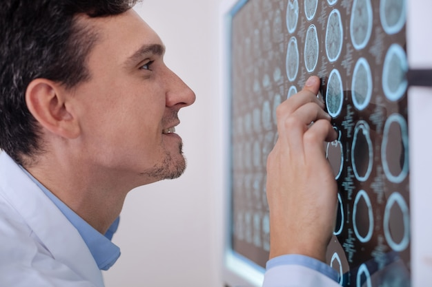 Vrolijke opgetogen mannelijke arts die naar de röntgenfoto kijkt en glimlacht terwijl hij geniet van zijn werk