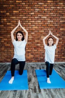 Vrolijke opgetogen vrouwen die op een yogamat zitten en ochtendoefeningen doen. in kamer met muren.