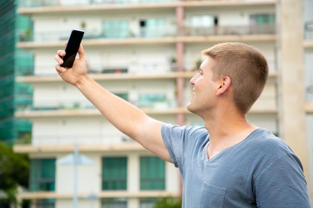 Vrolijke opgewekte studentenkerel die selfie in openlucht nemen
