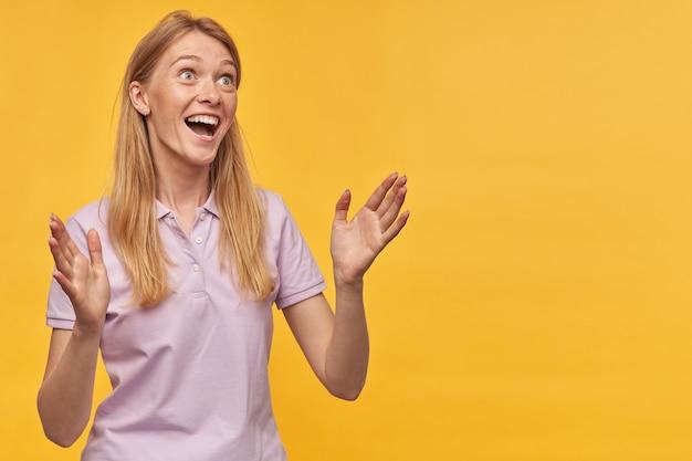 Vrolijke opgewonden blonde jonge vrouw met sproeten in lavendelt-shirt die lacht en applaudisseert over gele muur