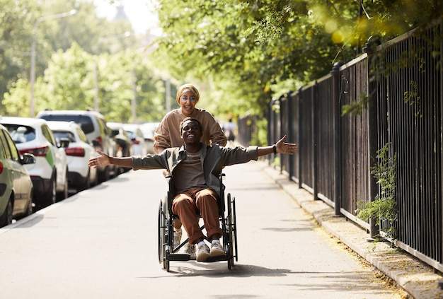 Vrolijke opgewonden jonge afro-amerikaanse gehandicapte man in rolstoel geduwd door een vrouw met uitgestrekte armen te laten rennen en vrijheid te voelen