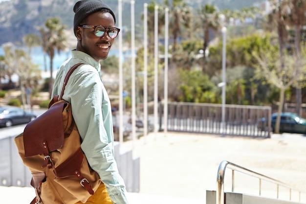 Vrolijke opgewonden jonge afro-amerikaanse toerist met rugzak wandelen langs verlaten straten van europa. stijlvolle stedelijke zwarte man op vakantie buitenlandse stad verkennen, op zoek met gelukkige glimlach