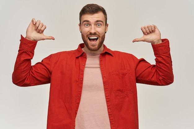 Vrolijke opgewonden jonge bebaarde man in rood overhemd permanent en wijzend op zichzelf met twee beide duimen overhandigt witte muur