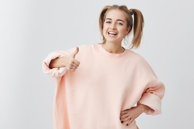 Vrolijke opgewonden jonge blanke vrouw met twee paardenstaarten, in roze trui, ok gebaar tonen en glimlachen, haar witte tanden demonstrerend, genietend van haar zorgeloze leven. alles is in orde!