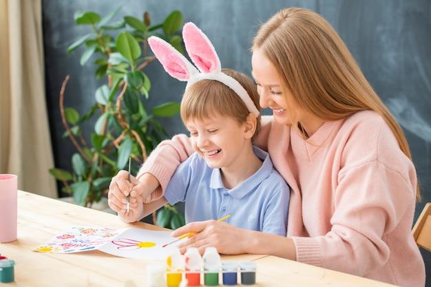 Vrolijke opgewonden jonge creatieve familie aan tafel zitten en genieten van pasen kaarttekening