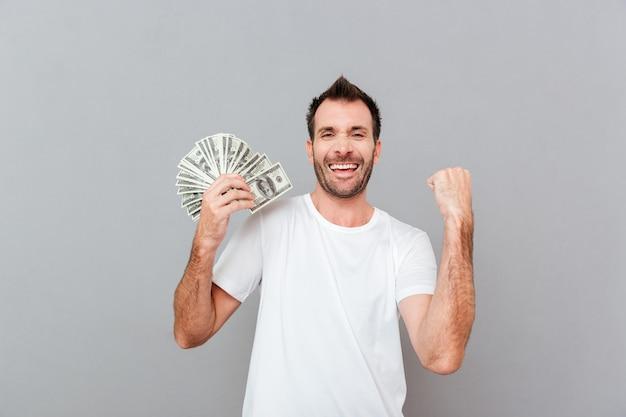 Vrolijke opgewonden jonge man die dollars vasthoudt en succes viert over grijze achtergrond