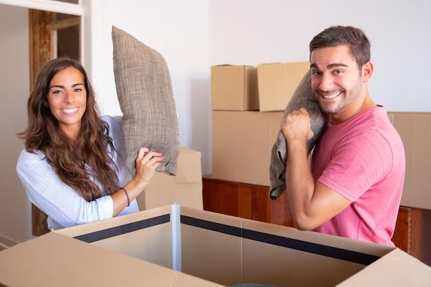 Vrolijke opgewonden jonge man en vrouw die kussens van een open kartonnen doos uitstappen, genieten van het verplaatsen en uitpakken van dingen