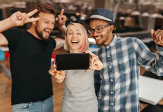 Vrolijke opgewonden jonge vrienden die plezier hebben en selfie nemen