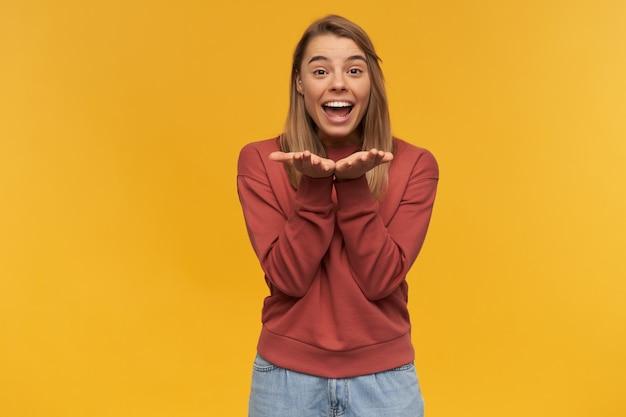 Vrolijke opgewonden jonge vrouw in vrijetijdskleding ziet er gelukkig uit en houdt lege handpalmen voor zichzelf boven de gele muur