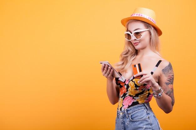 Vrolijke opgewonden jonge vrouw met mobiele telefoon en creditcard over gele achtergrond