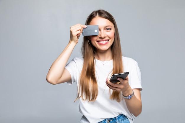 Vrolijke opgewonden jonge vrouw met mobiele telefoon en creditcard