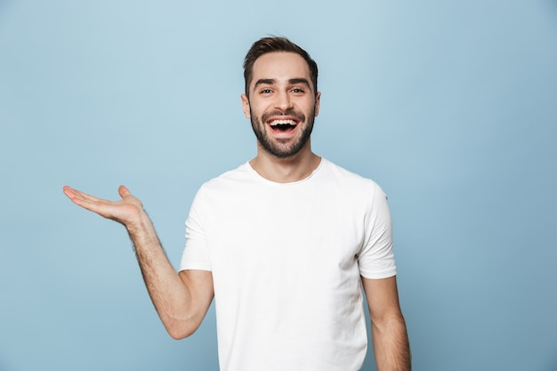 Vrolijke opgewonden man met een leeg t-shirt dat geïsoleerd over een blauwe muur staat en kopieerruimte presenteert