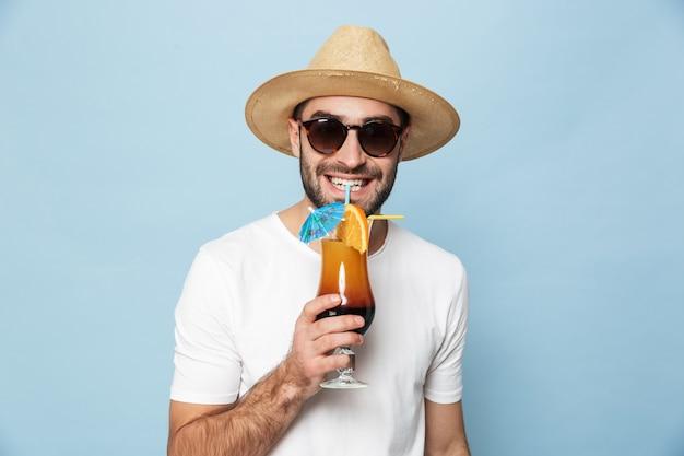 Vrolijke opgewonden man met een leeg t-shirt dat geïsoleerd staat over de blauwe muur, cocktail drinkt, plezier heeft