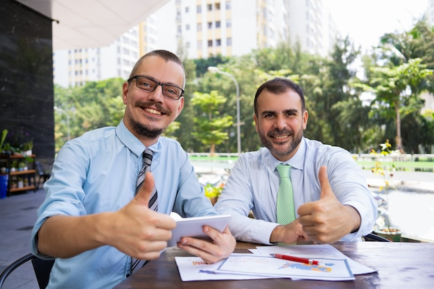 Vrolijke opgewonden ondernemers tonen thumbs-up