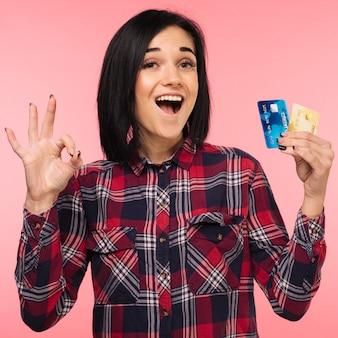 Vrolijke opgewonden verrast jonge vrouw met creditcard tonen zingen ok over roze achtergrond