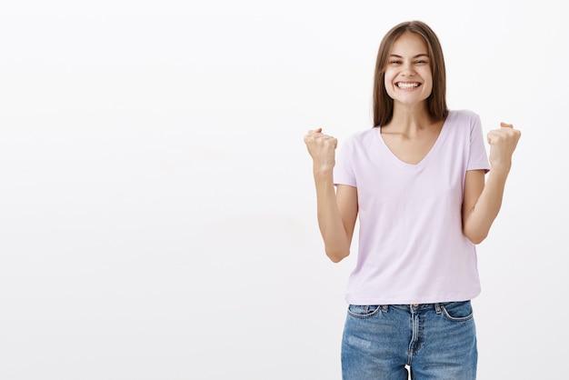 Vrolijke opgewonden vrouw die vuisten opheft en ja zegt, zich gelukkig en verrukt voelt met succes en overwinningsgebaar