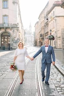 Vrolijke opname van een mooi echtpaar van middelbare leeftijd dat zich voor de camera stelt, terwijl ze hand in hand lopen op de trambaan op de stoep, in de oude oude stad. familie, liefde en mensen concept