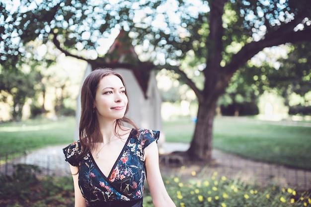 Vrolijke optimistische brunette in een bloemenjurk in het park