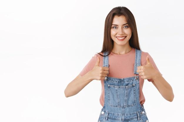 Vrolijke, optimistische brunette vriendin wroeten voor partner, duimen laten zien, aanmoedigen om het beste te doen, geloven dat ze kan winnen, breed glimlachen, iets goedkeuren of akkoord gaan, zoals concept, witte achtergrond