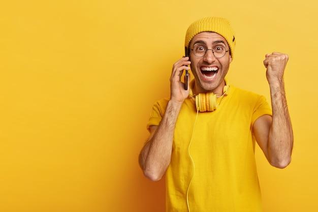 Vrolijke optimistische man met brede glimlach, triomfantelijk gebalde vuist opheft, roept via smartphone, geniet van gesprek