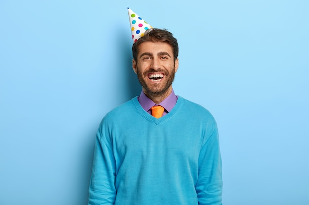 Vrolijke optimistische man met verjaardagshoed poseren in blauwe trui