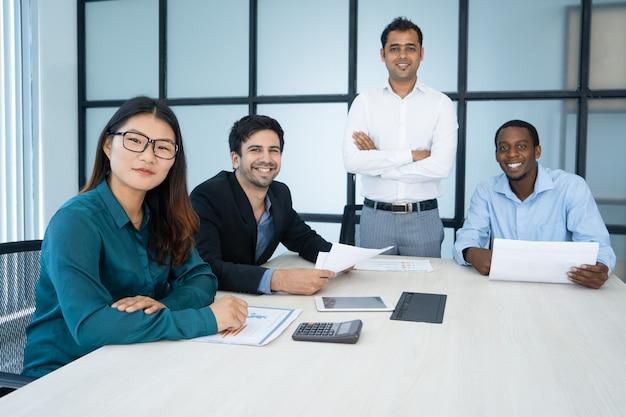 Vrolijke optimistische verkoopmanagers die rapport analyseren en camera in raadskamer bekijken.