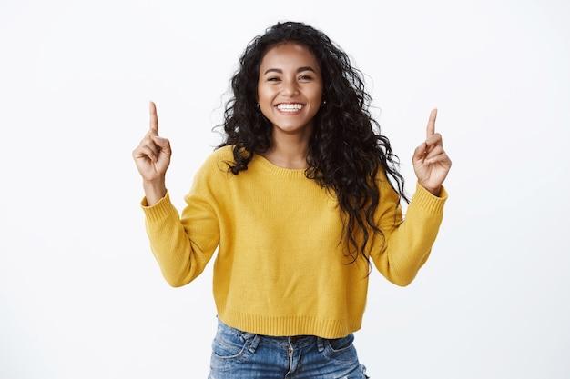 Vrolijke optimsitische jonge vrouwelijke student met krullend donker kapsel, gele trui, vrolijk lachend en lachend, wijzende vingers omhoog, vrienden laten linken naar site of kopieer ruimte, witte muur