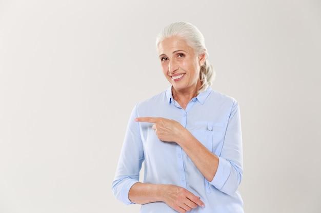 Vrolijke oude dame in blauw shirt, wijzend met de vinger op de lege copyspace