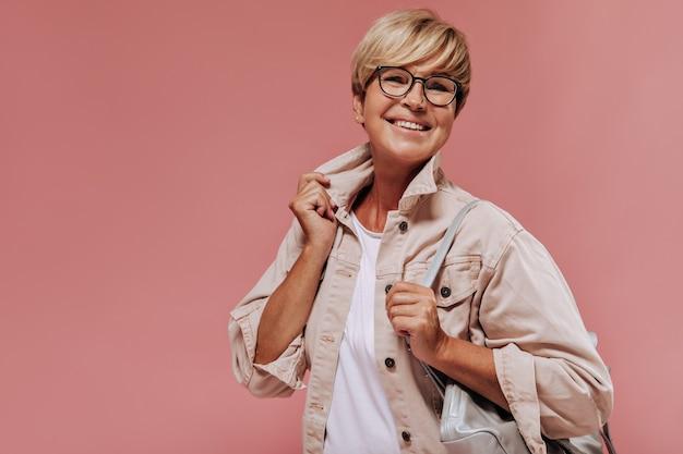 Vrolijke oude dame met blond kort kapsel en gebruinde huid in beige modern jasje glimlachend en koel tas op geïsoleerde achtergrond te houden.