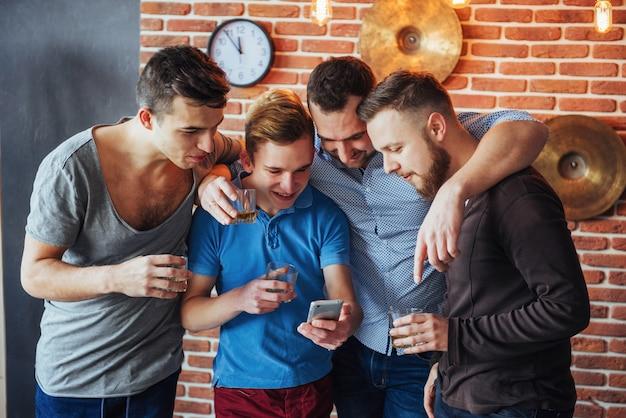 Vrolijke oude vrienden communiceren met elkaar en telefoneren, glazen whisky in pub. entertainment levensstijl. wifi verbonden mensen in bartafelvergadering