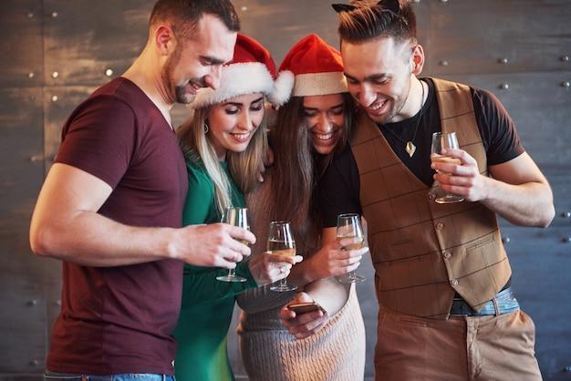 Vrolijke oude vrienden communiceren met elkaar en telefoneren, met glazen champagne in nieuwjaarsfeest. concept van entertainment en levensstijl. wifi verbonden mensen