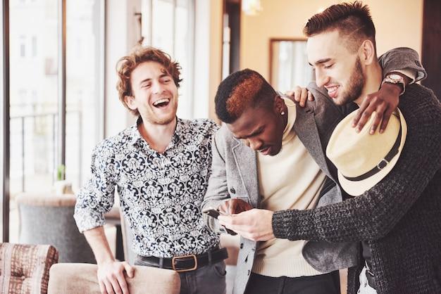 Vrolijke oude vrienden communiceren met elkaar en telefoon kijken in pub. concept van entertainment en lifestyle. wifi verbonden mensen in bartafelvergadering