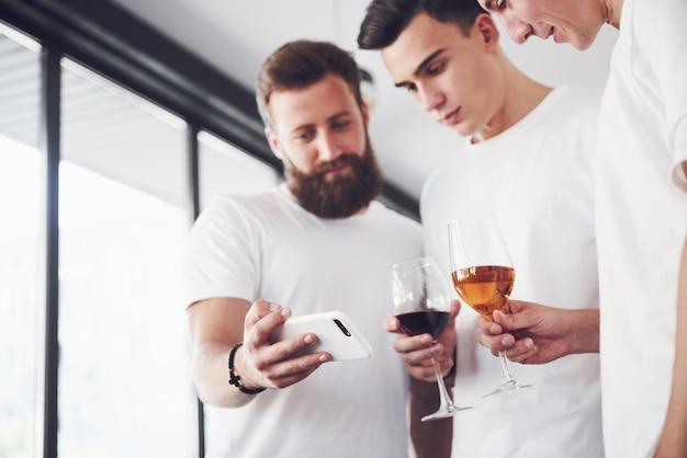 Vrolijke oude vrienden communiceren met elkaar en telefoon kijken, met glazen whisky of wijn in pub.