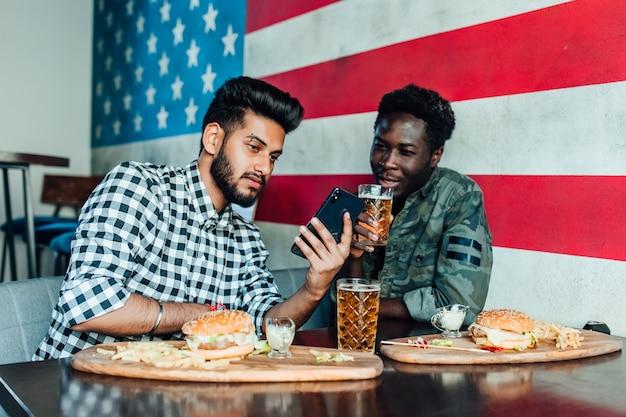 Vrolijke oude vrienden die plezier hebben met smartphone en tapbier drinken met hamburgers aan toog in pub.