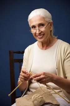 Vrolijke oude vrouw breien.