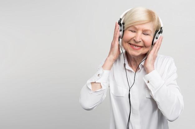 Vrolijke oude vrouw die aan muziek in hoofdtelefoons luistert. ze geniet van het moment.