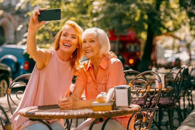 Vrolijke oude vrouw die met dochter op caféterras zit en poseert voor selfie